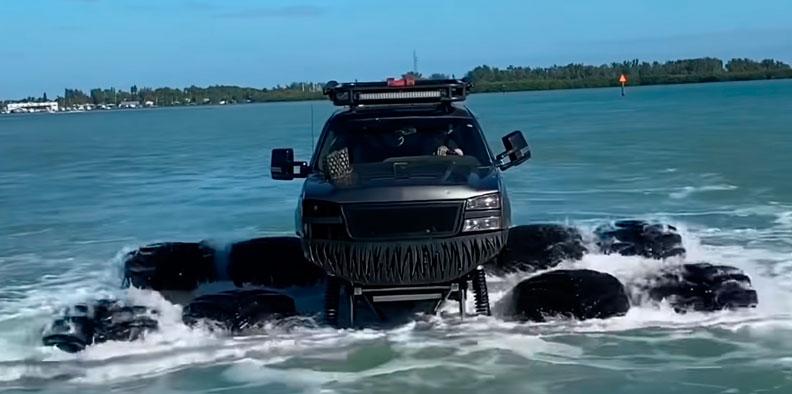 Машина на больших колёсах плывёт по воде